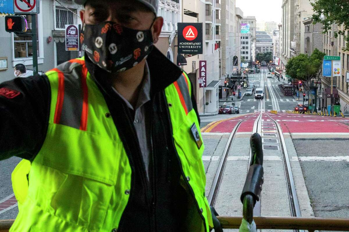 Conductor Jesus Villaseñor, early this month, operates Muni's first cable car in service since the start of the pandemic. Muni employees will be required to get vaccinated once a vaccine is fully approved by the U.S. Food and Drug Administration or risk losing their jobs.