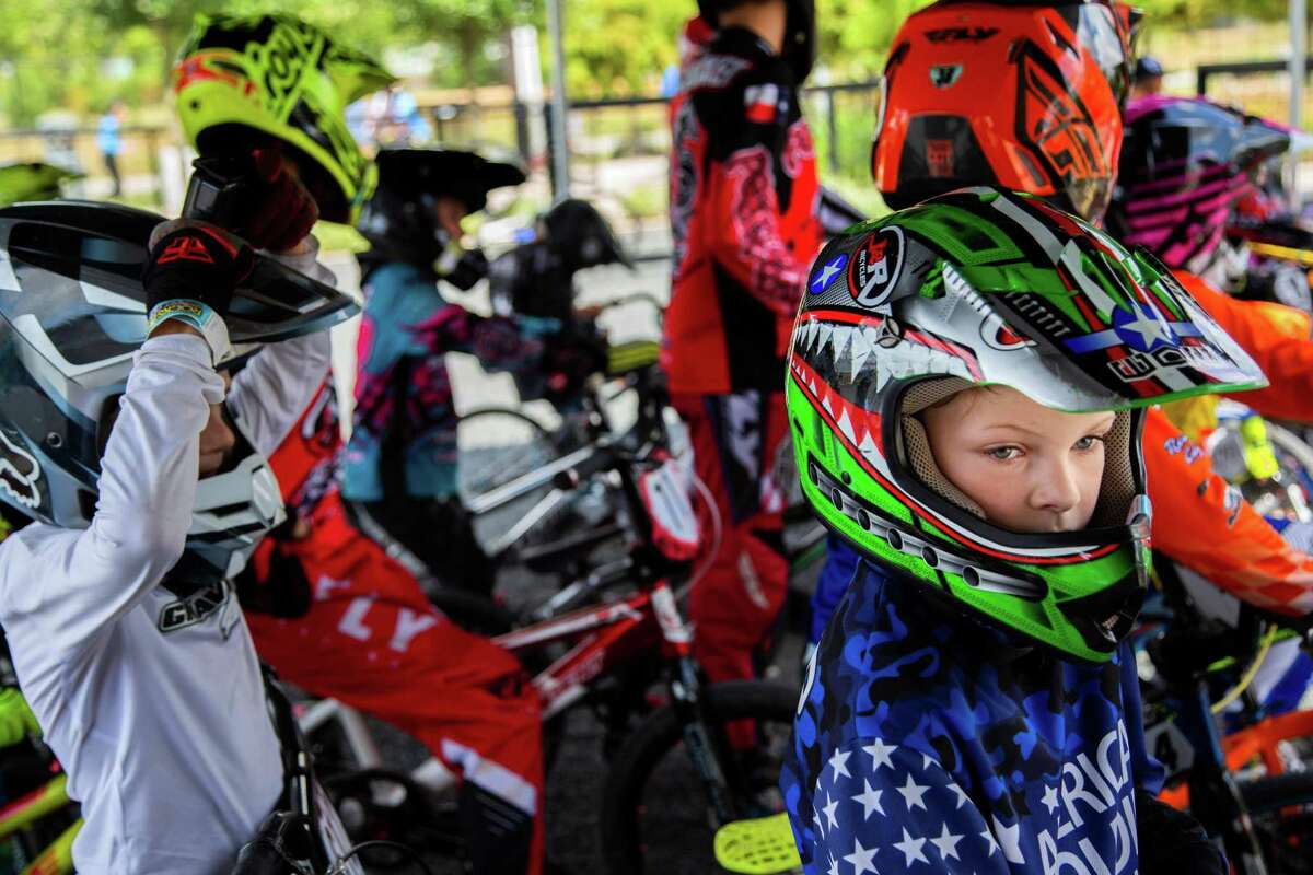 A group of competitors wait for their turn to race on their BMX bikes at the Rockstar Energy Bike Park, Saturday, Aug. 14, 2021, in Greenspoint.