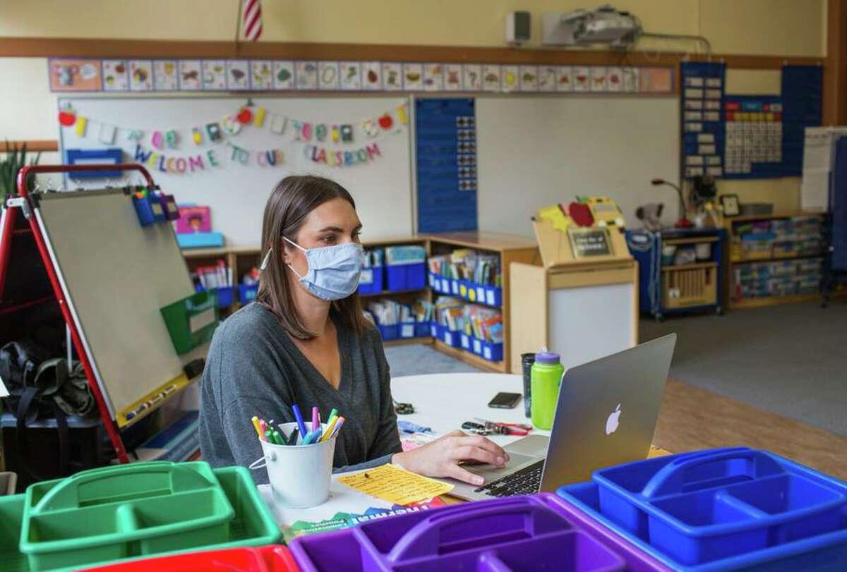 Kindergarten teacher Lauren Goss prepares her classroom before John Muir Elementary reopens after the shutdown.