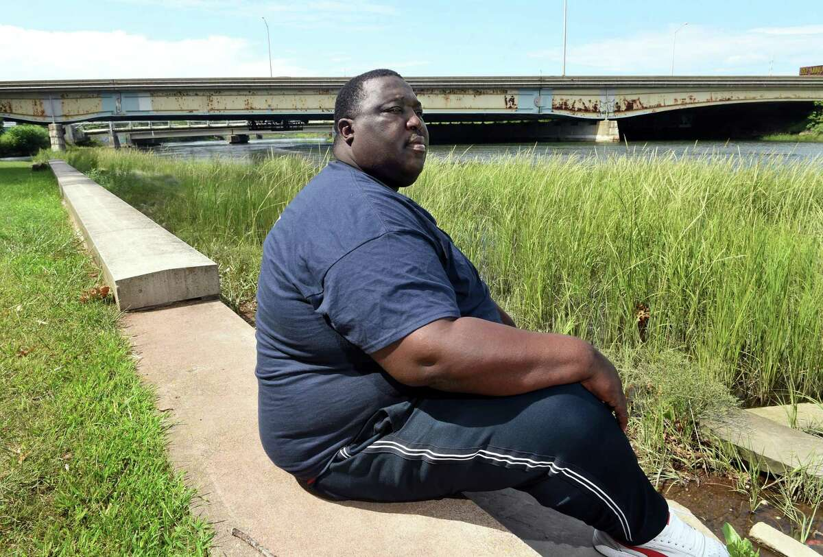 """William """"Juneboy"""" Outlaw III, lead street outreach worker for the Connecticut Violence Intervention Program, sits by the Quinnipiac River in New Haven on August 14, 2021. He grew up a few blocks away and routinely goes down to the river to ground himself."""