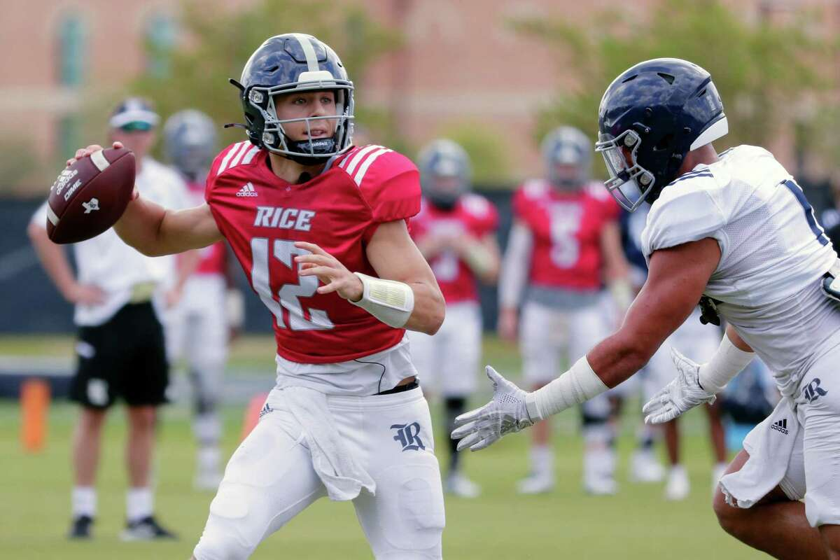 Quarterback Luke McCaffrey, left, looks to pass under pressure from Antonio Montero, right, during a Rice football scrimmage on the practice field Saturday, Aug. 14, 2021 in Houston, TX.