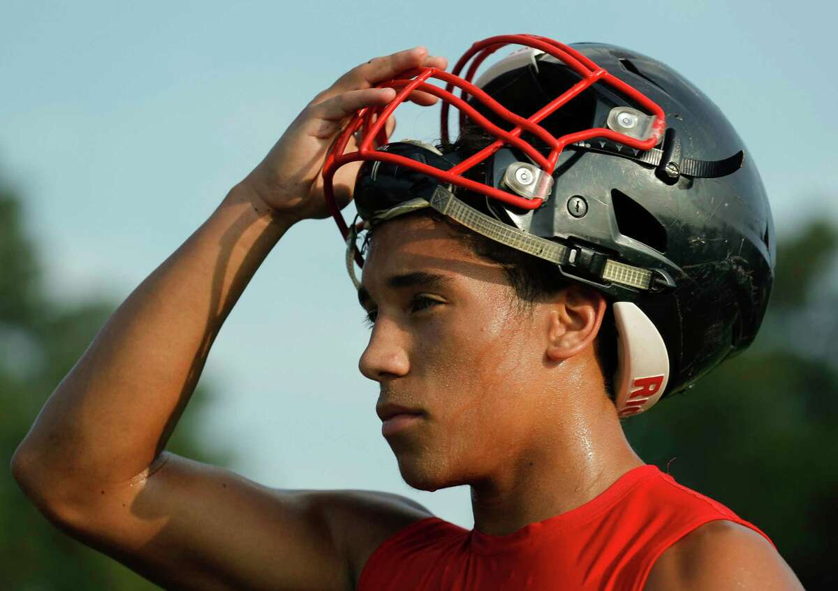 Running back John Milo takes a break during football practice at Caney Creek High School, Tuesday, Aug. 3, 2021, in Conroe.
