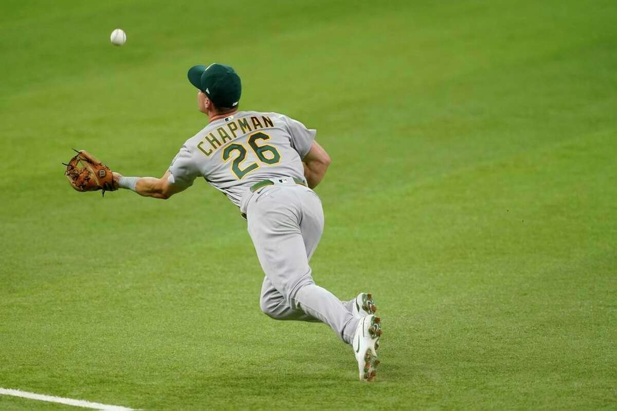 Oakland Athletics third baseman Matt Chapman makes a diving catch on a flyout by Texas Rangers' Brock Holt in the fifth inning of a baseball game in Arlington, Texas, Saturday, Aug. 14, 2021. (AP Photo/Tony Gutierrez)