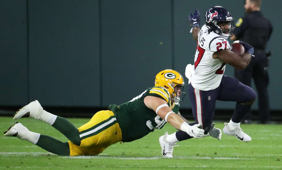 \Houston Texans running back Scottie Phillips (27) is tripped up by Green Bay Packers defensive tackle Jack Heflin (90) during the second quarter of an NFL pre-season football game Saturday, Aug. 14, 2021, in Green Bay, Wis.