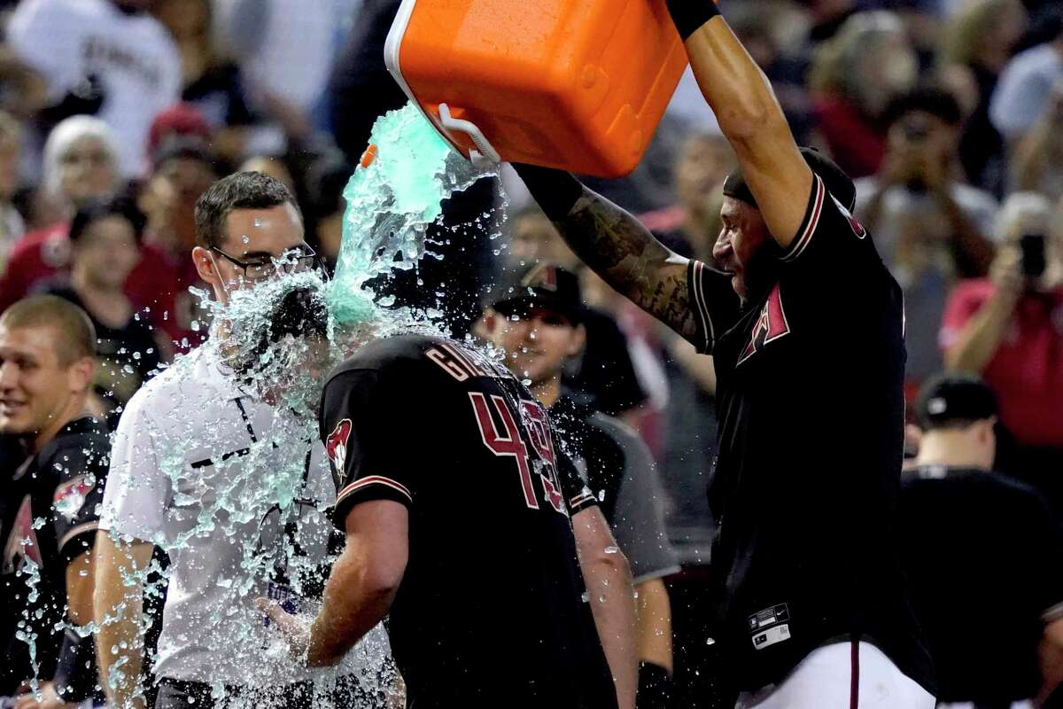 Arizona Diamondbacks left fielder David Peralta, right, soaks starting pitcher Tyler Gilbert after his no-hitter against the San Diego Padres in a baseball game Saturday, Aug. 14, 2021, in Phoenix. It was Gilbert's first career start. The Diamondbacks won 7-0.