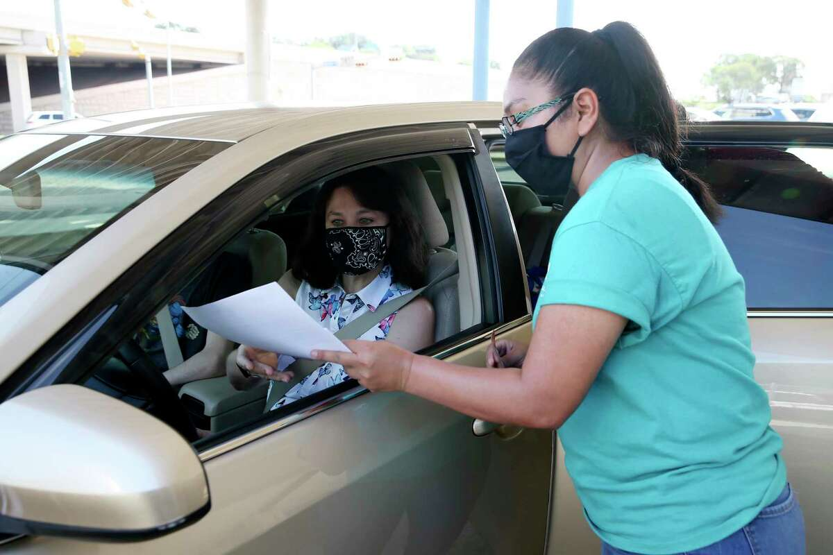 Lucinda Crane, 53, gets her delivery paperwork from Meals on Wheels San Antonio Community Engagement Coordinator Soh Soh Estrada. It is a family tradition. She took over the route from her father. Her son Gregory helps out with the delivery.