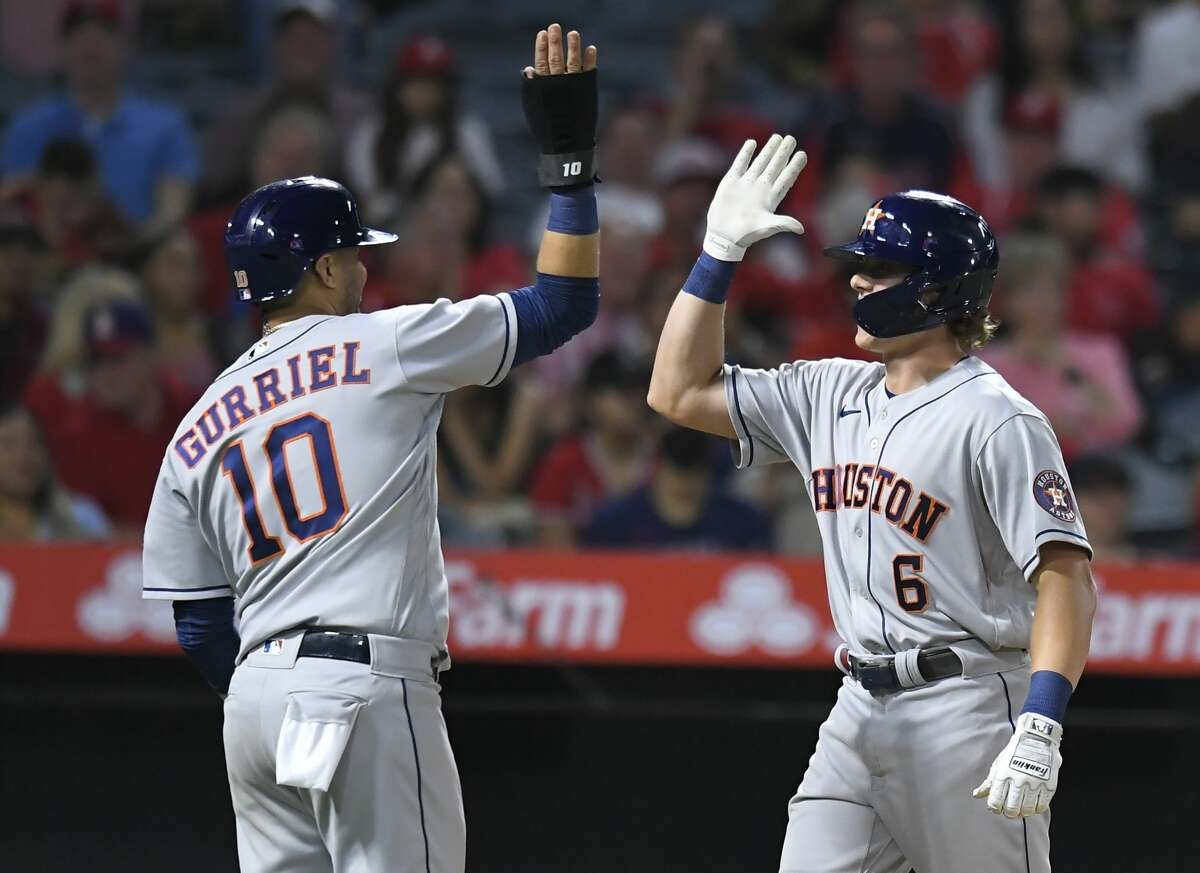 Houston Astros' Yuli Gurriel, left, congratulates Jake Meyers for his grand slam in the sixth inning while playing against the Los Angeles Angels in a baseball game Saturday, Aug 14, 2021, in Anaheim, Calif. (AP Photo/John McCoy)