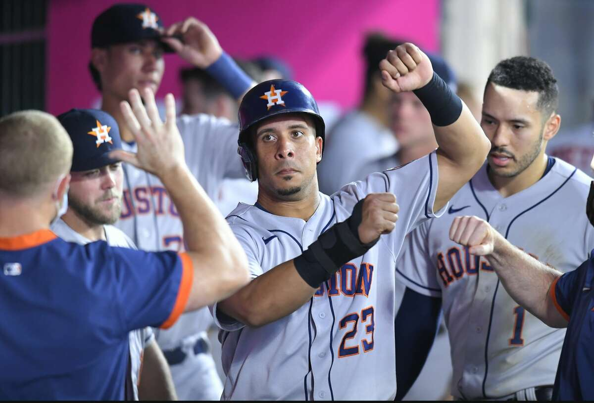 Houston Astros' Michael Brantley is congratulated after he scored on a triple by Yordan Alvarez in the fifth inning against the Los Angeles Angels in a baseball game Saturday, Aug 14, 2021, in Anaheim, Calif.