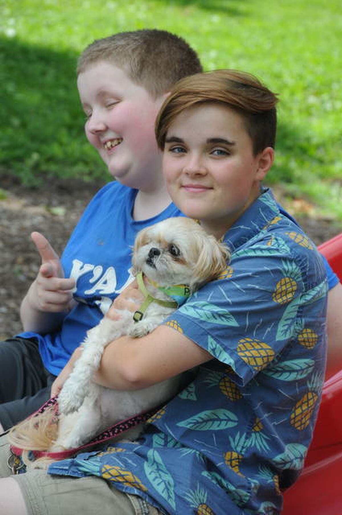 Deidrick and Esmond Hicks take a Pawty break Saturday with Esmond's dog Kyky. The first-ever event in the Roxana Park raised funds for L&L Animal Warriors.