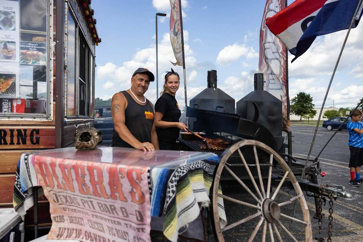 Dave Olvera, left, and Katelynn Gotham, right, pose in front of the grill during a Food Truck Festival Saturday, August 14, 2021 at the Midland Towne Center. (Drew Travis/for the Daily News)