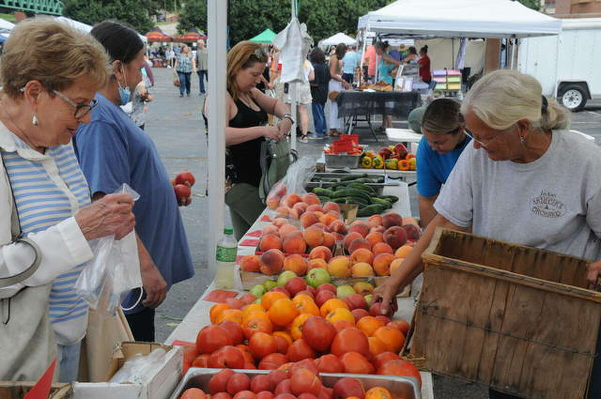 JoAnn Kreuger, right, puts out more fresh produce at the Kreuger's Orchards booth Saturday at the weekly Alton Farmers' and Artisans' Market on the riverfront.