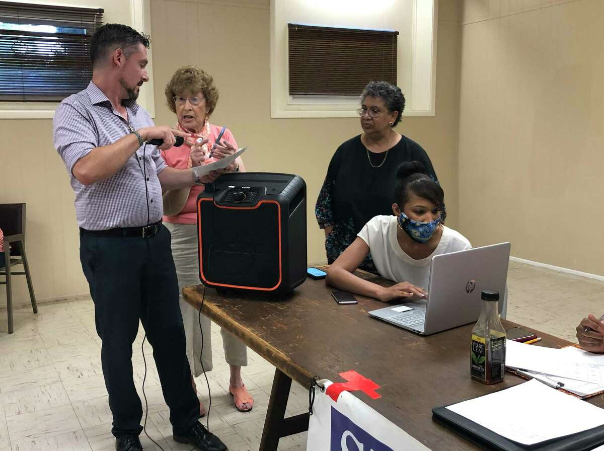 Stratford Democratic Town Committee Chairman Steve Taccogna, left, talks to a party member as mayoral candidate Stephanie Philips, standing at right, looks during an endorsement meeting at the Universalist Unitarian Church July 21, 2021.