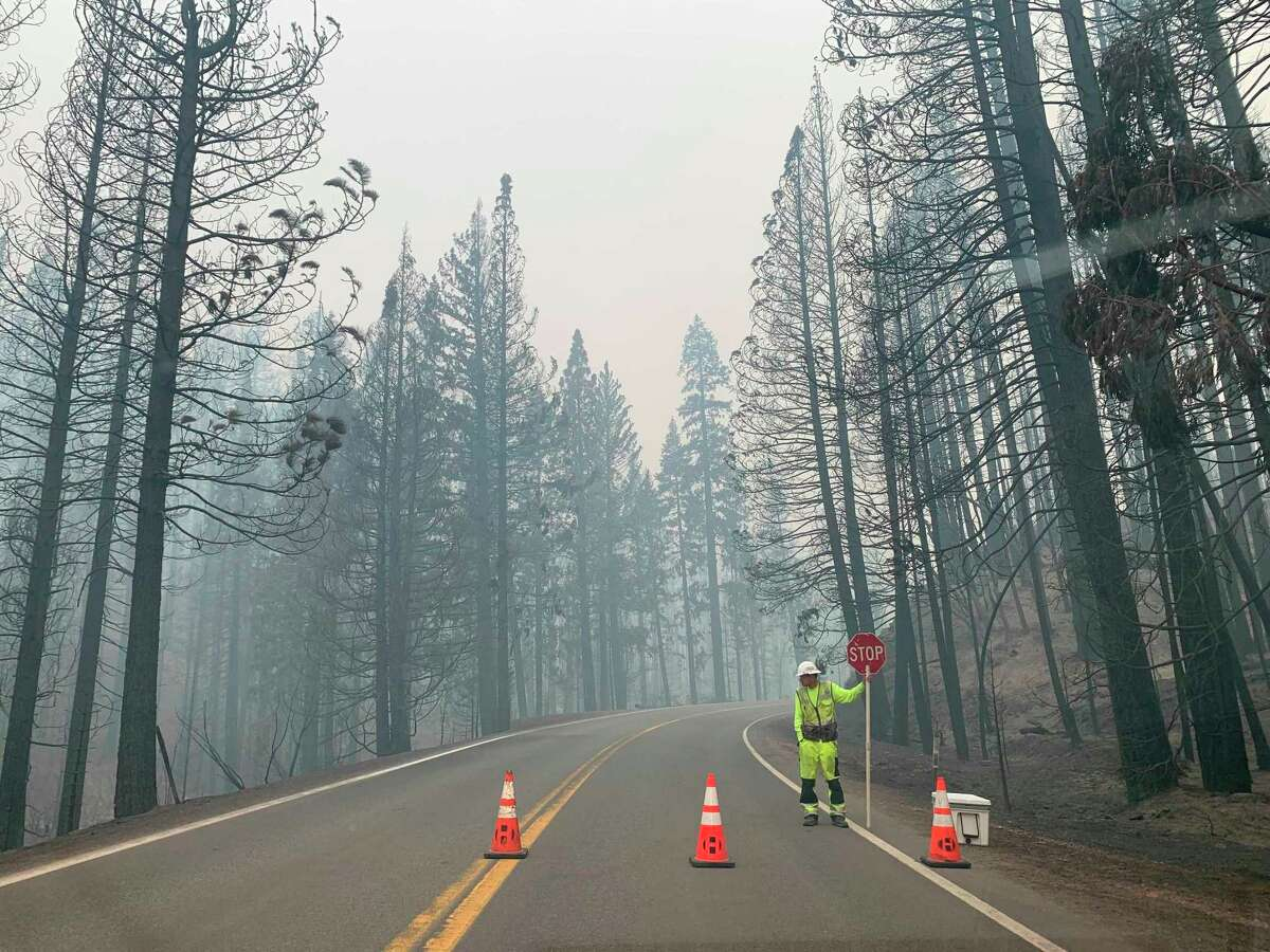 A worker blocks Highway 89 to Canyondam in Plumas County due to risk from the Dixie Fire, which also continues to rage across three other Northern California counties.