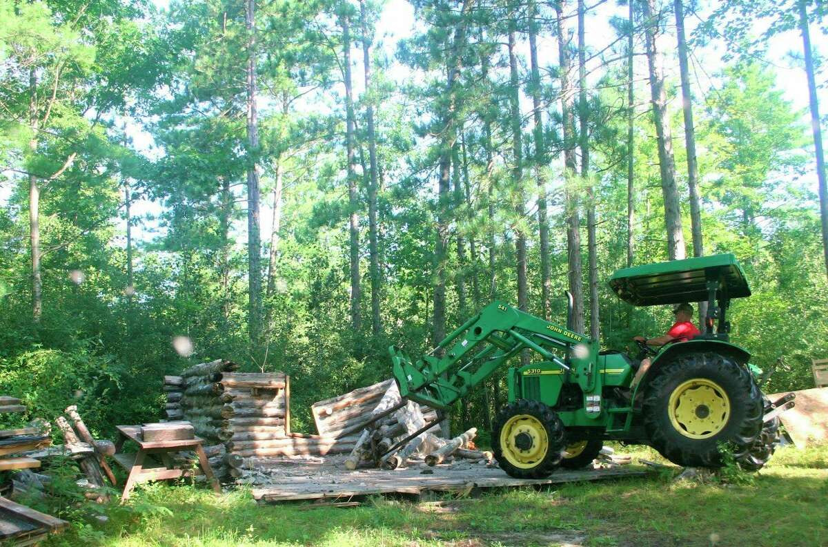 Scout leader Joel Schultz uses a forklift to knock down part of the wall of the cabin structure at White Pine Valley Recreation Area. Several scout leaders with Troop 114 spent the past few weeks demolishing the structure. (Pioneer photo/Cathie Crew)