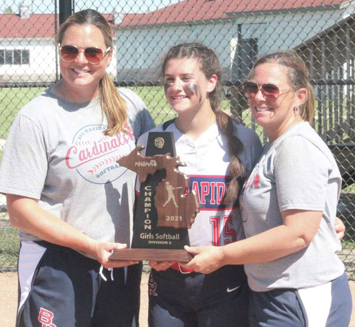 Big Rapids' Alanah Thompson holds the Cardinal district championship trophy in June with coach Dawn Thompson and assistant coach Jenny Prince (left). (Pioneer file photo)