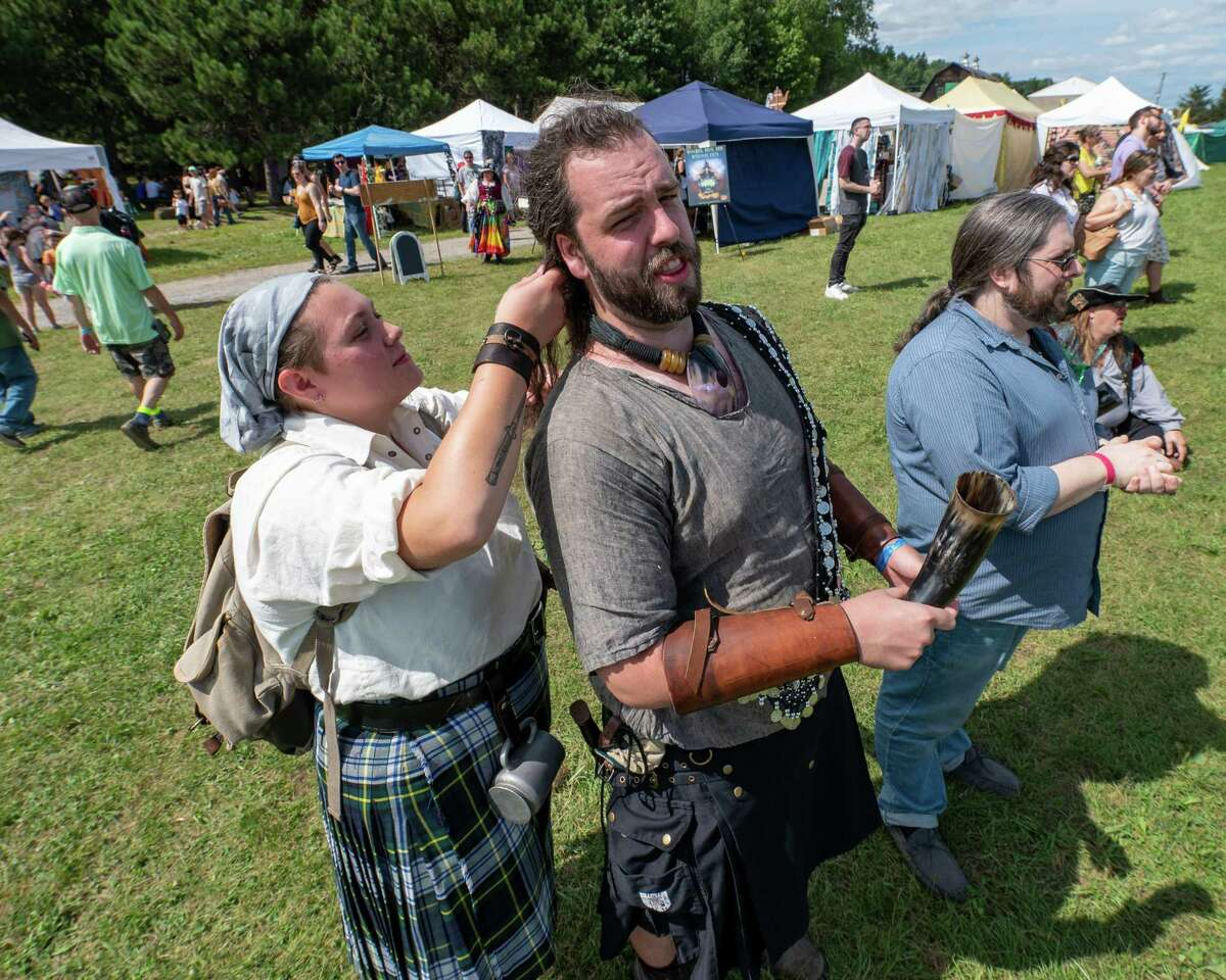 Ava Grande braids the hair of Japhid Moses during the Renaissance Festival at Indian Ladder Farms Apple Orchard in Altamont, NY, on Sunday, Aug. 15, 2021 (Jim Franco/Special to the Times Union)