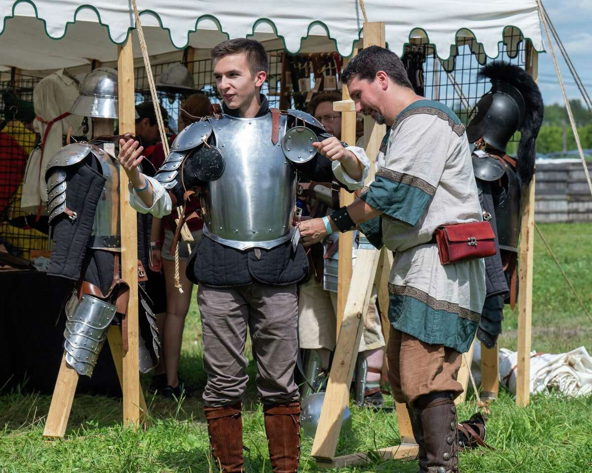 Caleb Hand, of Made by Hand Leather, fits Brendan Mahoney in a suit of armor at the Renaissance Festival at Indian Ladder Farms Apple Orchard in Altamont, NY, on Sunday, Aug. 15, 2021 (Jim Franco/Special to the Times Union)