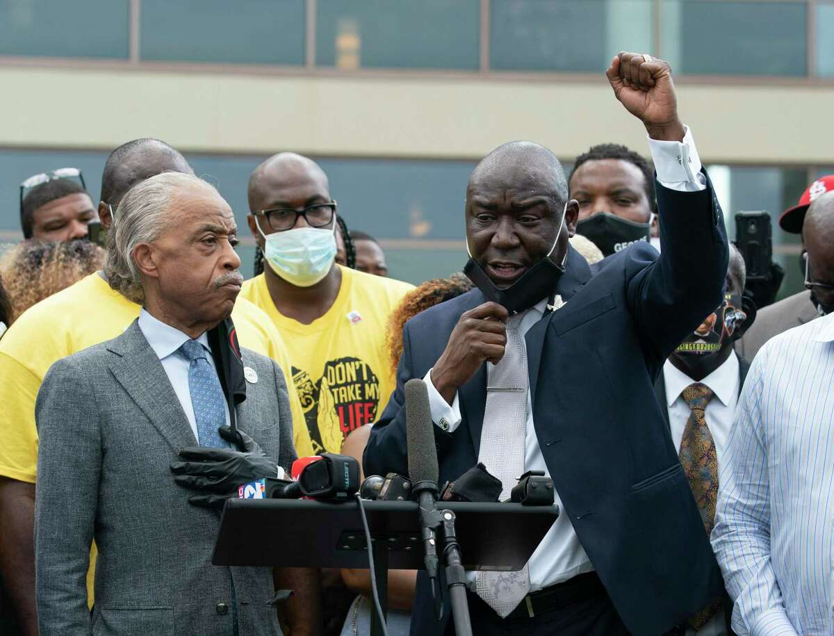 Benjamin Crump, right, the main attorney for George Floyd's family, raises his first while speaking in a press conference with Rev. Al Sharpton, left, and Floyd's brothers, in yellow, Monday, June 8, 2020, at The Fountain of Praise Church in Houston.