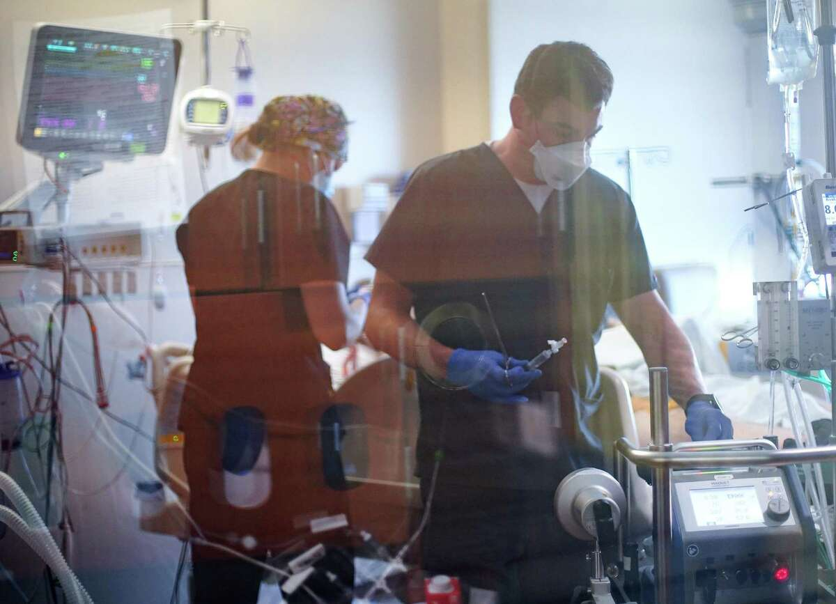 Nurses work on a COVID-19 patient, who is in his 20's, at UTMB Galveston's ICU on Wednesday, Aug. 11, 2021.
