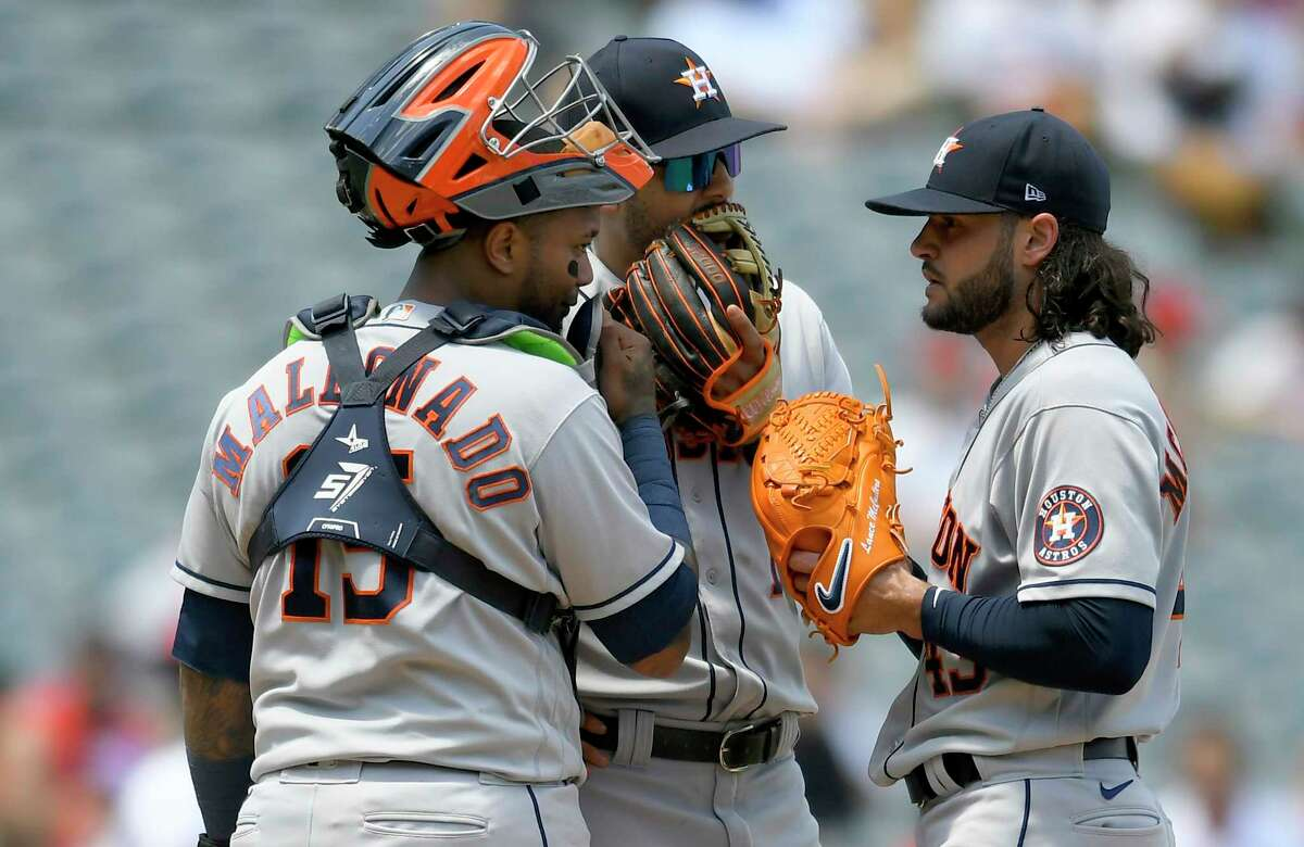 ANAHEIM, CA - AUGUST 15: Martin Maldonado #15 of the Houston Astros and Carlos Correa #1 talk to Lance McCullers Jr. #43 before he faces Shohei Ohtani #17 of the Los Angeles Angels in the second inning at Angel Stadium of Anaheim on August 15, 2021 in Anaheim, California.