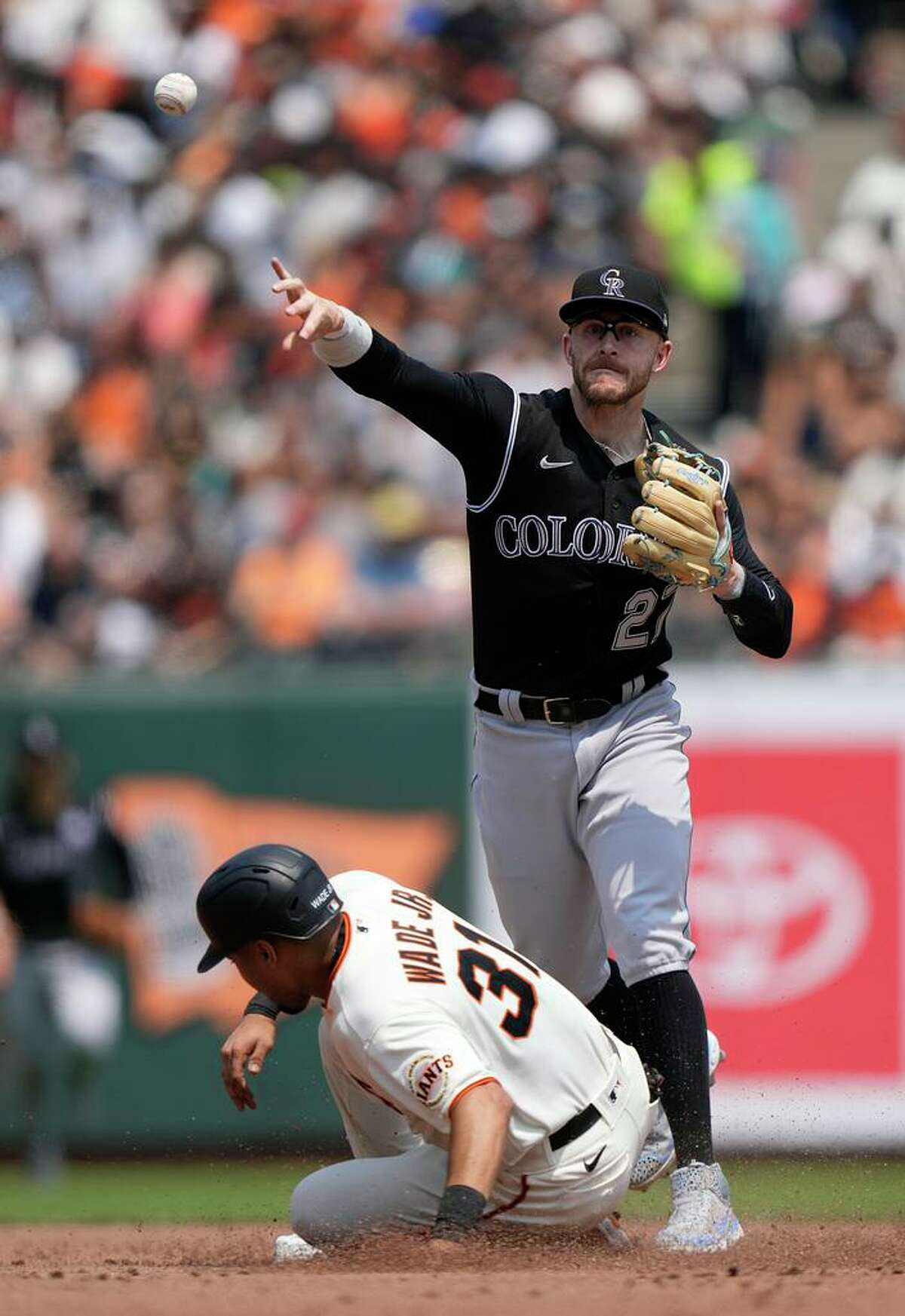 SAN FRANCISCO, CALIFORNIA - AUGUST 15: Trevor Story #27 of the Colorado Rockies completes the double-play throwing over the top of LaMonte Wade Jr #31 of the San Francisco Giants in the bottom of the third inning at Oracle Park on August 15, 2021 in San Francisco, California. (Photo by Thearon W. Henderson/Getty Images)