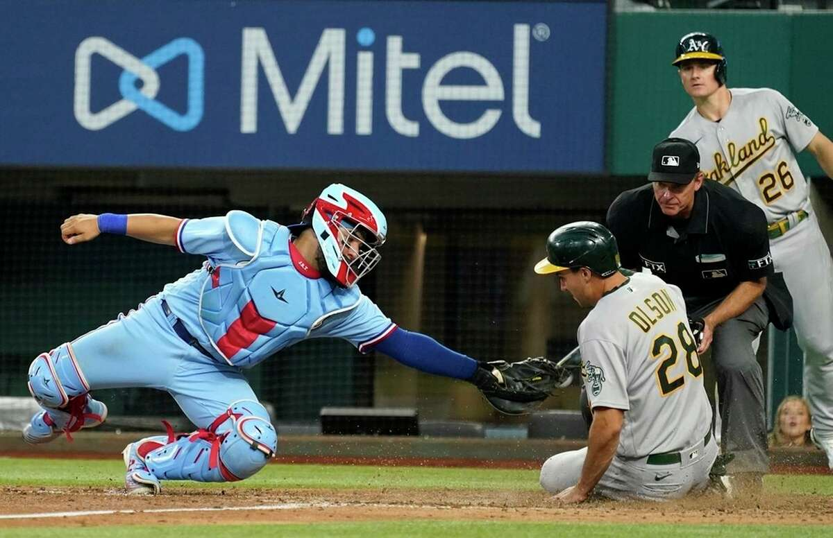 Rangers catcher Jose Trevino tries to tag A's first baseman Matt Olson, who slides home safely after Sean Murphy's eighth-inning double in Arlington, Texas. Olson had walked to reach base.