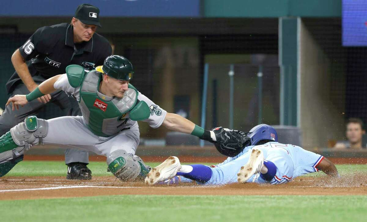 ARLINGTON, TX - AUGUST 15: Yonny Hernandez #65 of the Texas Rangers dives head first to home plate to score as Sean Murphy #12 of the Oakland Athletics applies the tag and umpire Ed Hickox #15 looks on during the first inning at Globe Life Field on August 15, 2021 in Arlington, Texas. (Photo by Ron Jenkins/Getty Images)