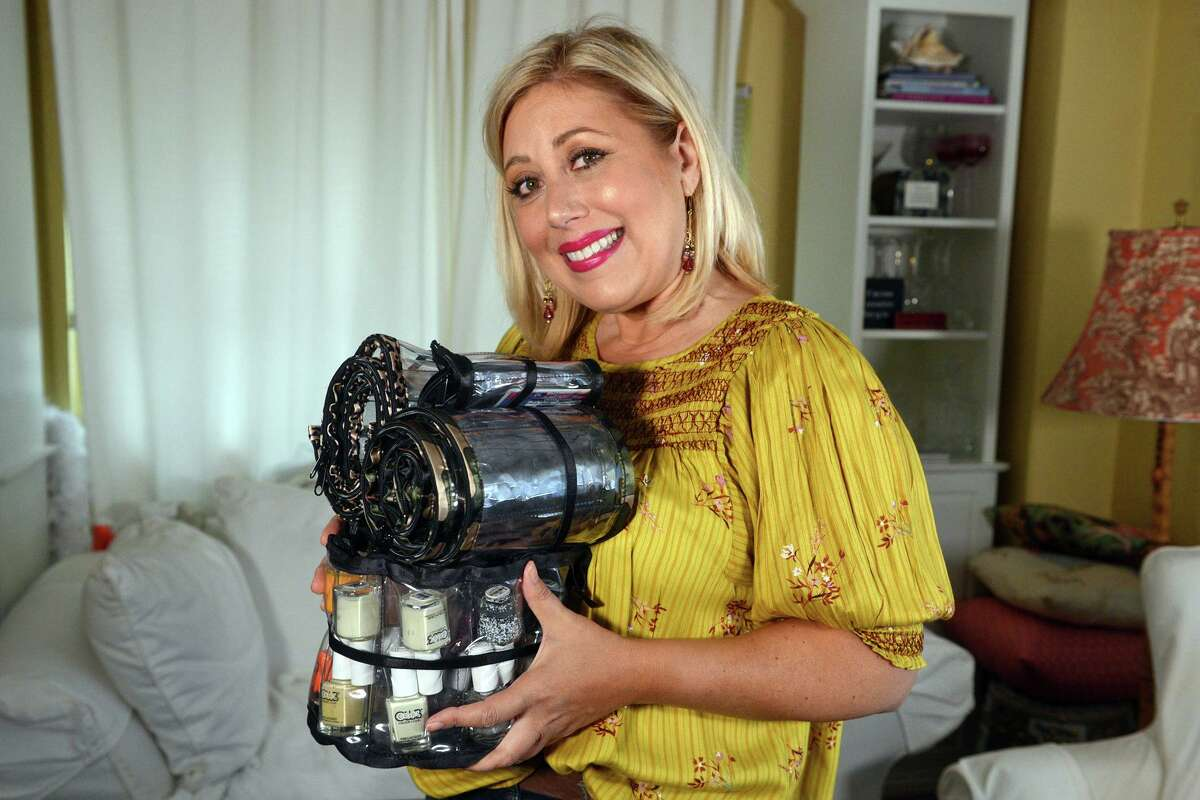 Sharon Lynn poses with some samples of her Glam Roll-Ups products in her home in Milford.
