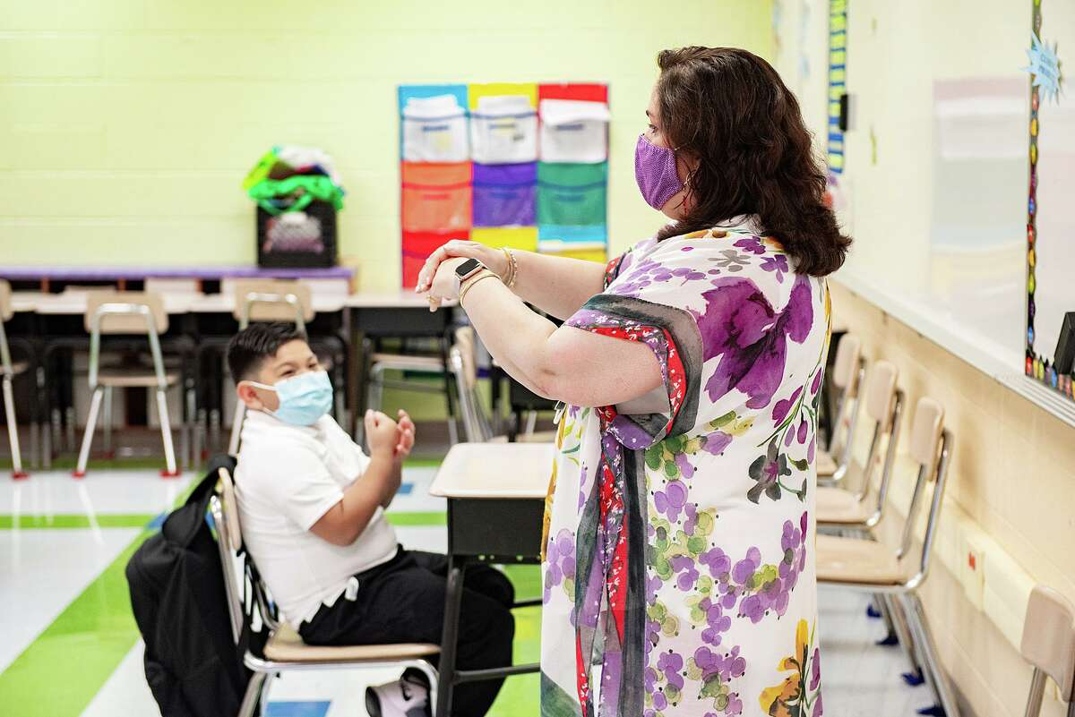 M.S. Ryan Elementary School student Elas Lozano mimics Counselor Judith Puig as they discuss proper hand washing technique, Aug. 24, 2020, during the first day back to school for some students during the COVID-19 Coronavirus pandemix.