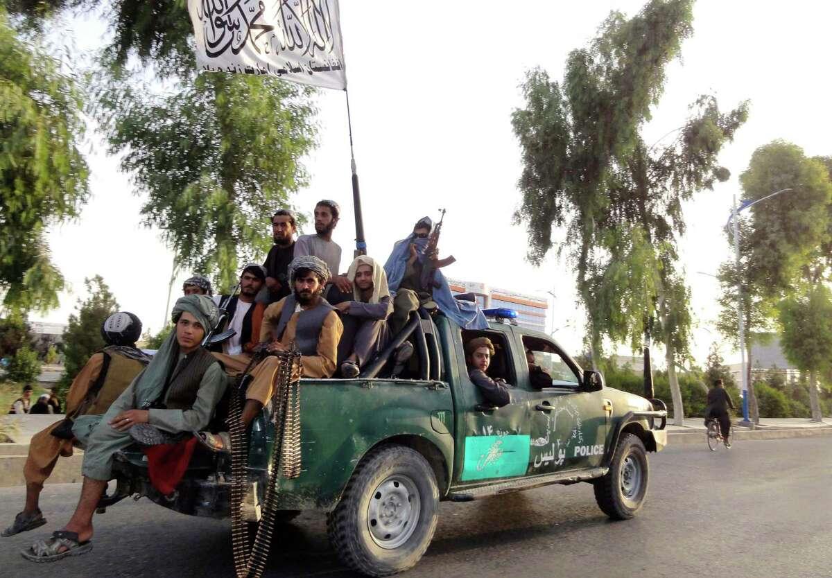 Taliban fighters patrol inside the city of Kandahar, southwest Afghanistan, on Sunday.