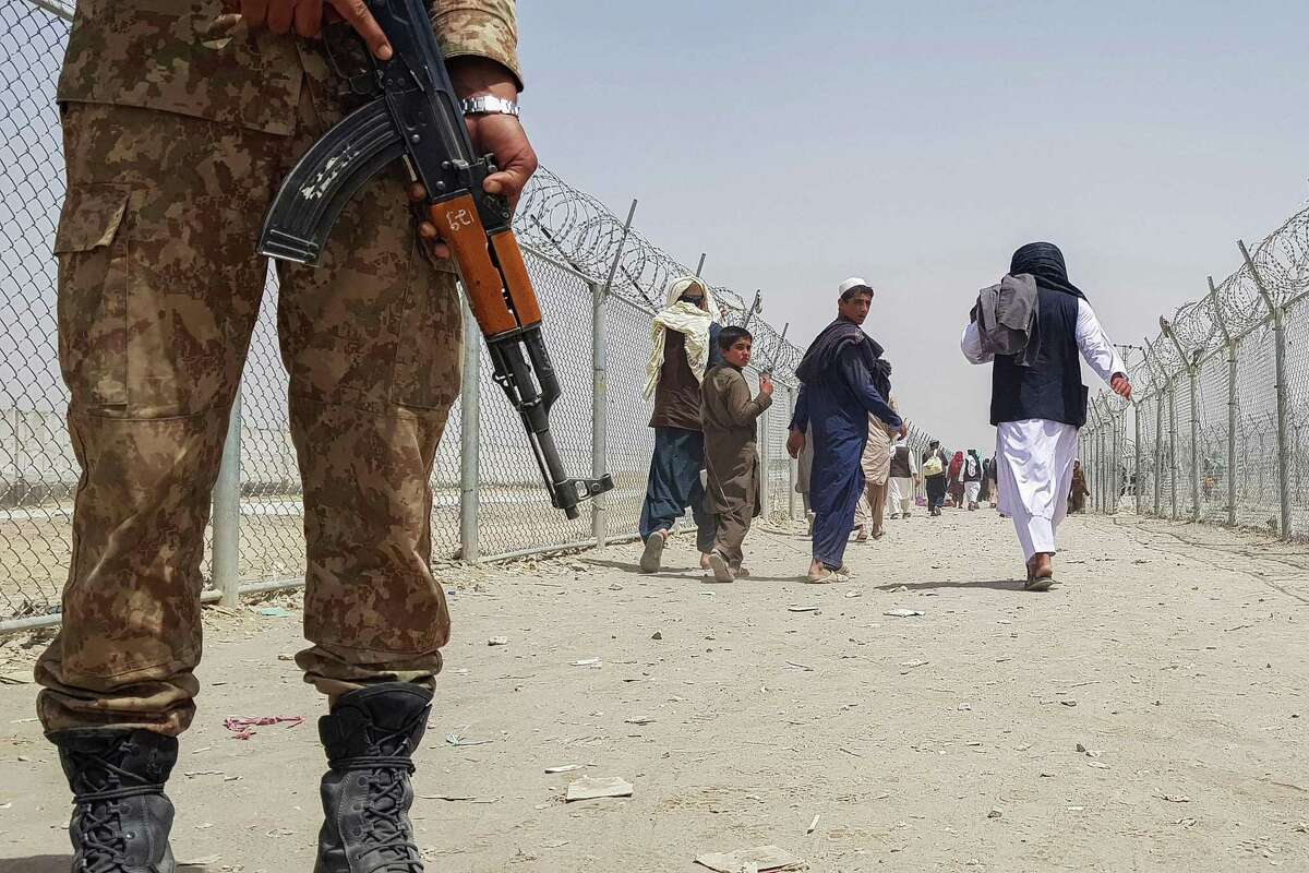 A Pakistani soldier stands guard at the border as stranded Afghans return to Afghanistan after the Taliban took control of the border town of Chaman. Afghan residents of the Bay Area are fearful for their relatives and friends still living in Afghanistan.