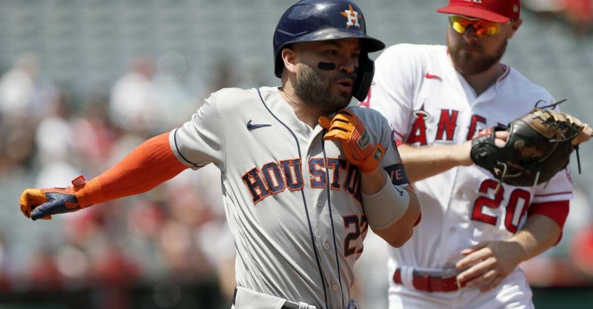 Los Angeles Angels first baseman Jared Walsh, right, tags out Houston Astros' Jose Altuve, left, on a bunt attempt during the first inning of a baseball game in Anaheim, Calif., Sunday, Aug. 15, 2021. (AP Photo/Alex Gallardo)