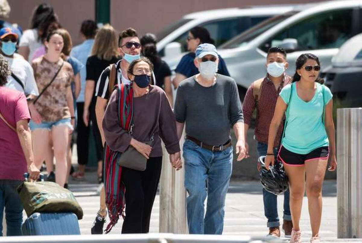 People wear masks as they walk near a park.