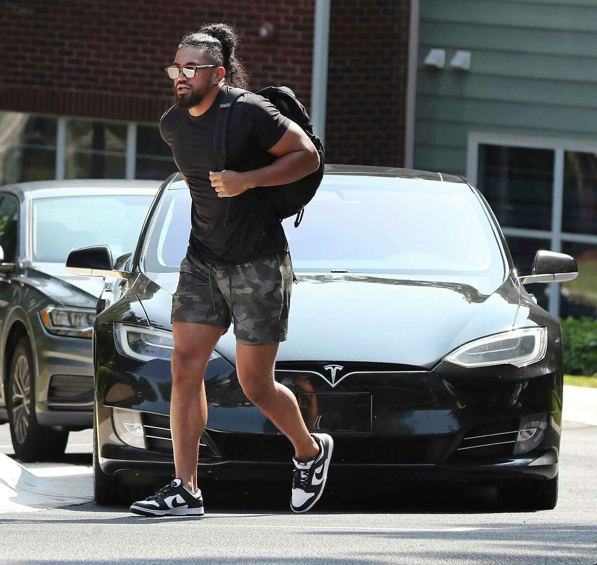 Atlanta Falcons linebacker Jacob Tuioti-Mariner walks in front of the Tesla he arrived in for NFL football training camp in Flowery Branch, Ga., Tuesday, July 27, 2021. (Curtis Compton/Atlanta Journal-Constitution via AP)