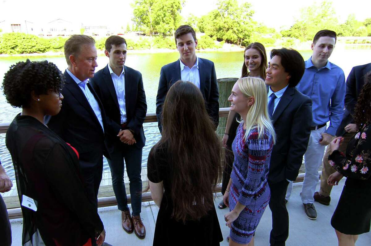 Gov. Ned Lamont, second from left, mingles in June 2021 with participants in the CTNext 2020 cohort of the Governor's Innovation Fellowship, in Stamford, Conn. Heading into the 2022 fiscal year that kicked off in July, the Connecticut Innovations venture fund has added consumer products companies to its investment criteria.