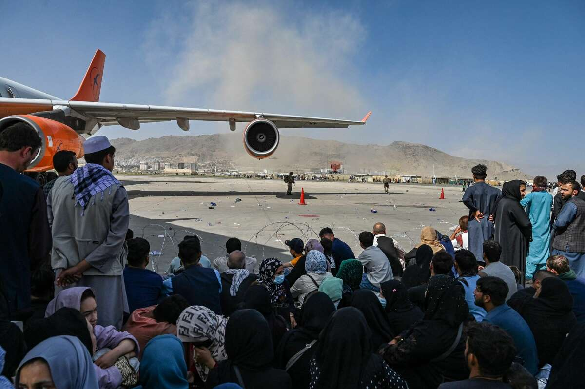 Afghans are seen sitting on the tarmac of the Kabul Airport on Monday hoping to find a way out of the Afghanistan, which has been taken over by the Taliban. A San Antonio man's wife and children are among those scrambling to find a way out of the country.
