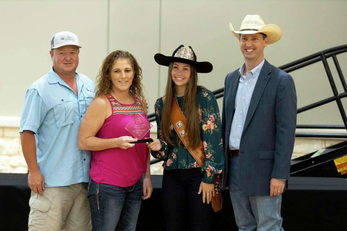 Morgan McGee, Montgomery County Fair Queen 2021, center right and MCFA Executive Committee president Cody Bartlett, right, poses for a portrait with 20-year Junior Non-Livestock auction buyers, North Montgomery County Support Group during The Montgomery County Fair Association annual Awards Dinner at the Lone Star Convention Center, Saturday, Aug. 14, 2021, in Conroe.