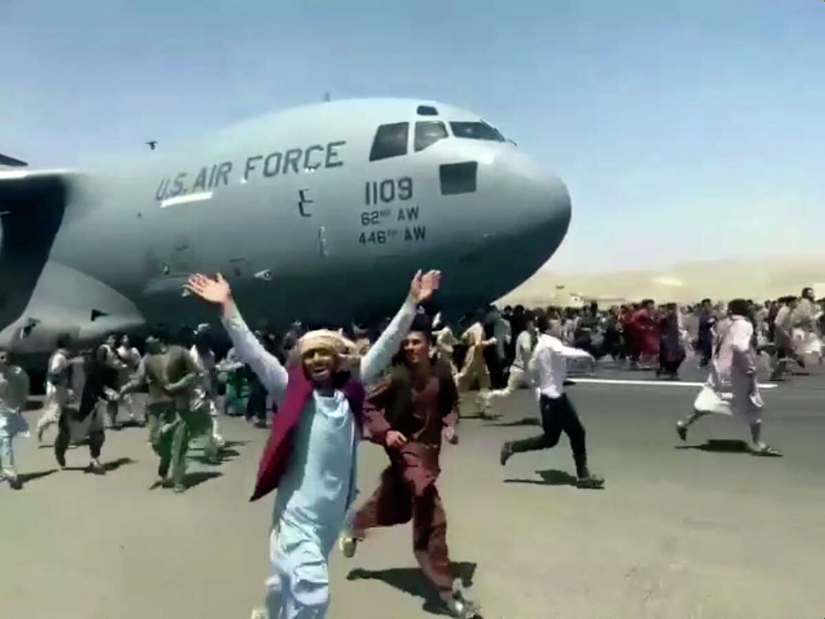Hundreds of people run alongside a U.S. Air Force C-17 transport plane as it moves down a runway of the international airport, in Kabul, Afghanistan, Monday, Aug.16. 2021. Thousands of Afghans have rushed onto the tarmac of Kabul's international airport, some so desperate to escape the Taliban capture of their country that they held onto an American military jet as it took off and plunged to death. (Verified UGC via AP)