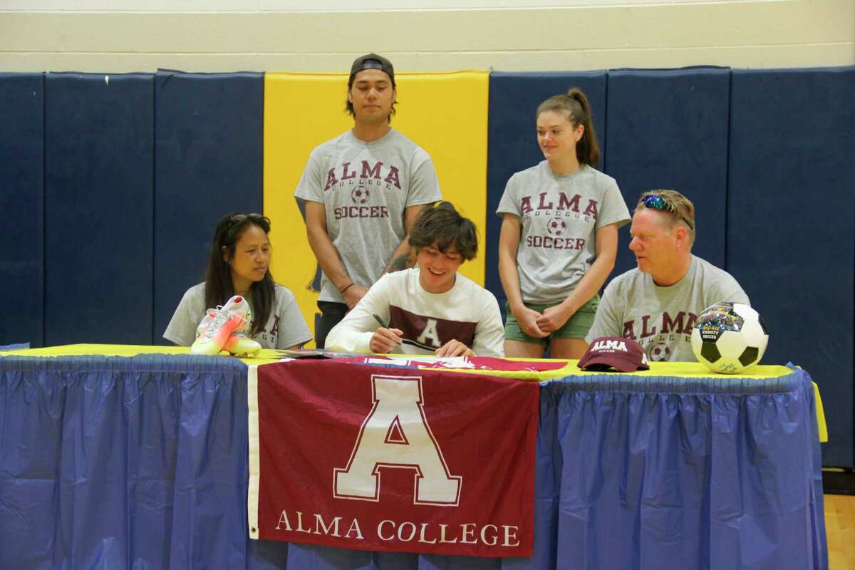 Bad Axe boys soccer player Kai Whipple is surrounded by family members as he signs his commitment letter to play mens soccer at Alma College. Whipple has been a key part of Bad Axe's recent run of success in boy's soccer. (Robert Creenan/Huron Daily Tribune)