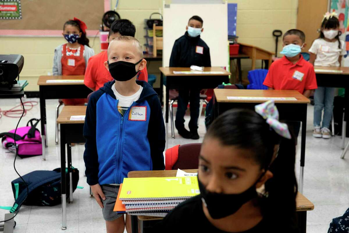 Colten Sapp practices standing with his hands at his side before he and the rest of his first grade class are taken through the hall of Pearce Elementary on the first day of school. As local officials battled with the governor in court amid constantly changing directions to public schools over mask-wearing, most kids arrived at Pearce wearing masks.