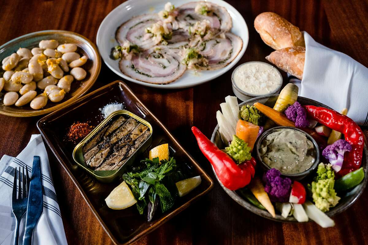 Pictured from left to right Beans a la Buvette, Pork belly porchetta, Pain Deep baguette and butter, crudités and Brisling some of the food on offer at Chezchez in San Francisco on Friday, August 13, 2021.