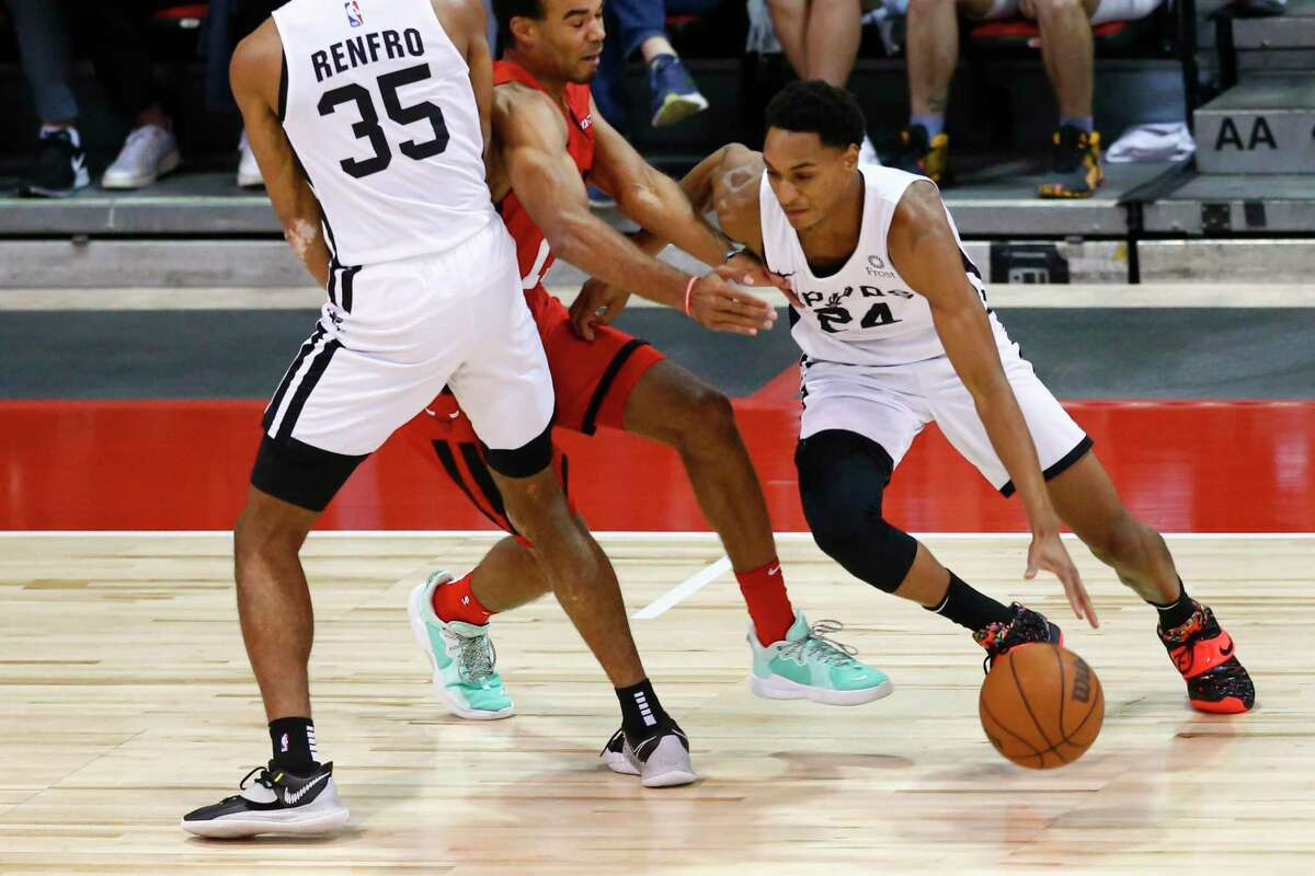 The Spurs' Devin Vassell (24) drives the ball around the Chicago Bulls' Jerome Robinson during the first half of an NBA summer league game in Las Vegas on Tuesday, Aug. 10, 2021.