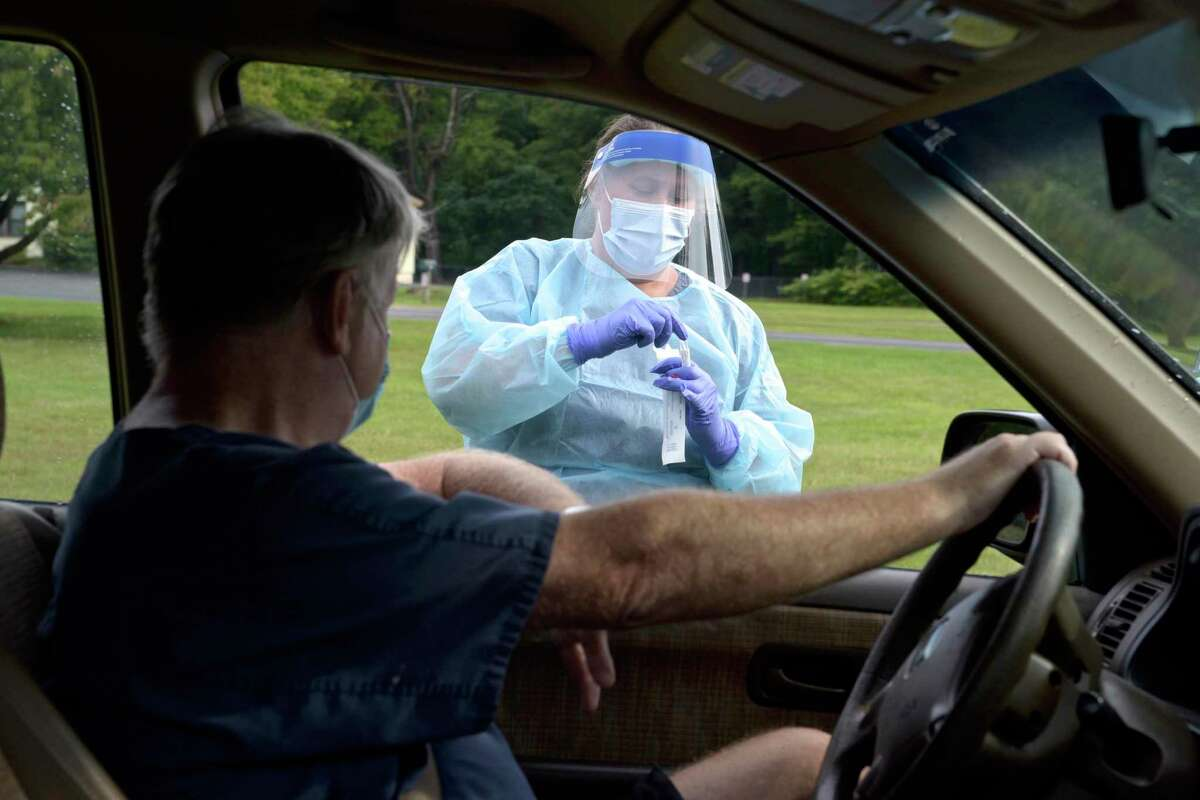 Nurse Heidi Bettcher collects a self administered COVID test from Bob Brophy, of New Milford, during the first day of the New Milford Health Department's COVID-19 drive-thru testing site at John Pettibone Community Center. Wednesday, August 11, 2021, New Milford, Conn.