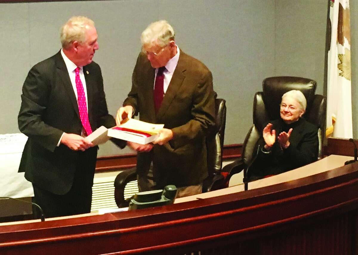 R-Collinsville, at left, presents retiring state Sen. William Haine, D-Alton, with a flag flown over the U.S. Capital for his retirement at the Madison County Administration buildings on Thursday. Both elected officials started their elected careers in Madison County, Shimkus as Treasurer and Haine as a County Board member and later state?'s sttorney.