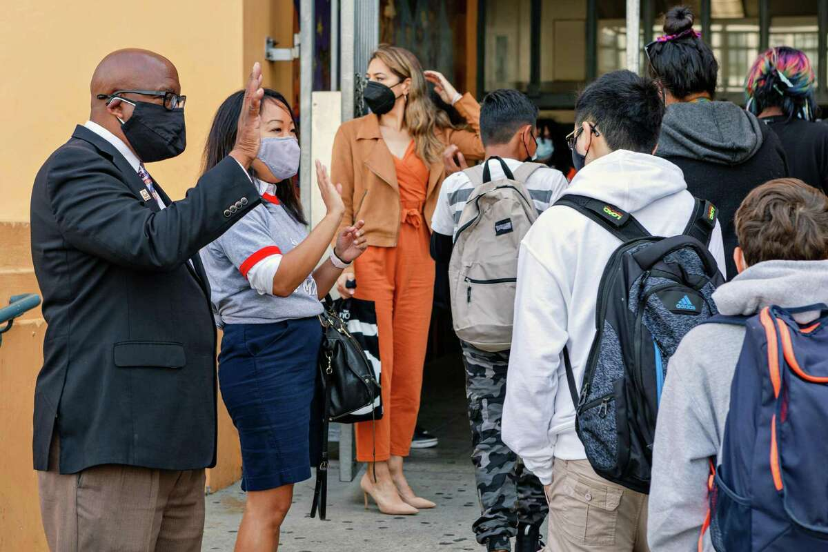 San Francisco schools Superintendent Dr. Vincent Matthews (left) and officials and school board members greet students as school begins at Everett Middle School. The state education superintendent is intervening to address the S.F. district's dire financial situation.