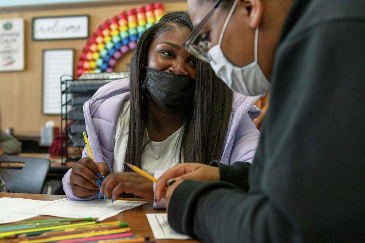 Lonyah Morris speaks with fellow student Kaeloni Parks on the first day back at Everett Middle School in San Francisco.