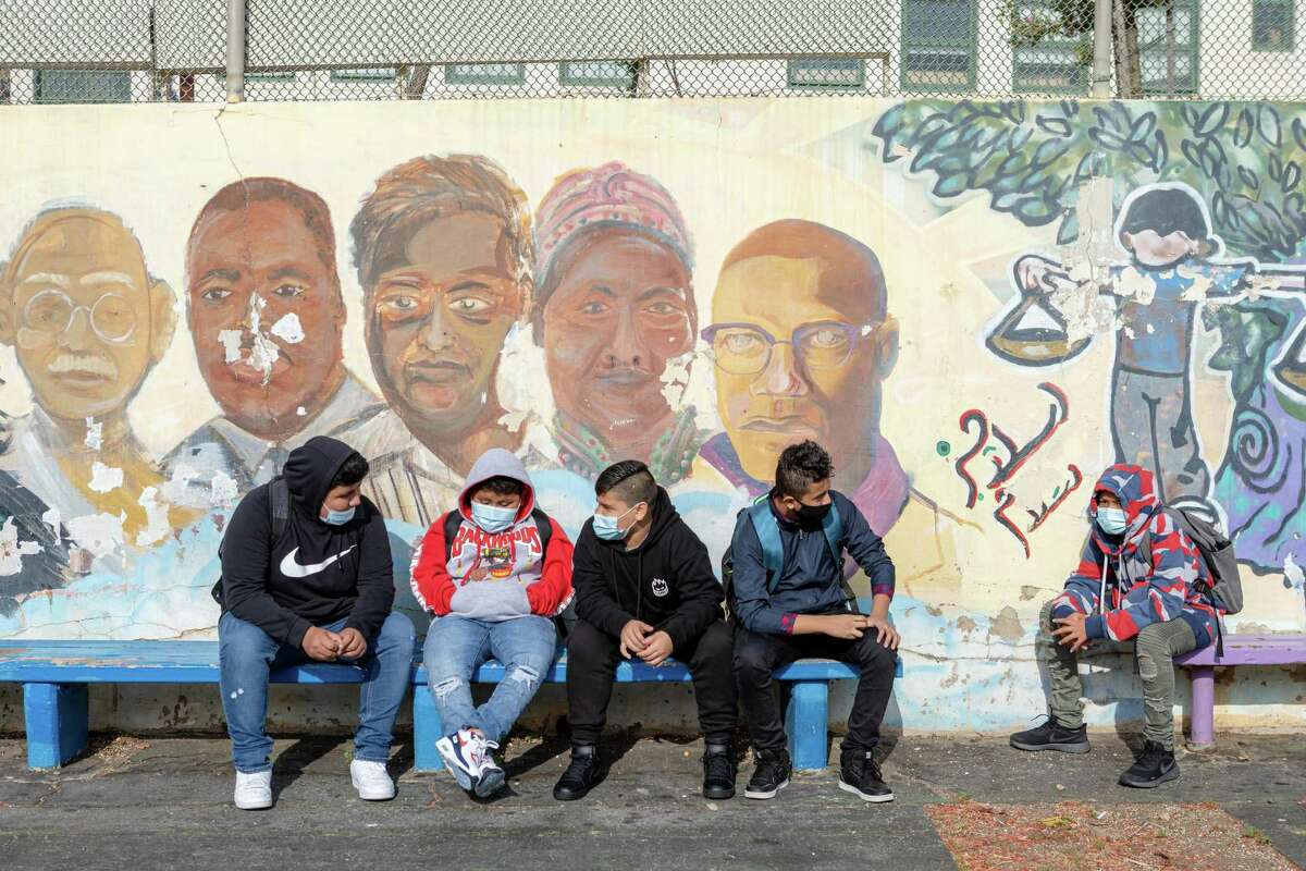 Everett Middle School students Jefferson Hernandez (left to right), Hector Manueles, Luis Hernandez, and Ever Iqui spend time in the schoolyard before the start of class on the first day of full time, in-person instruction in San Francisco, Calif.