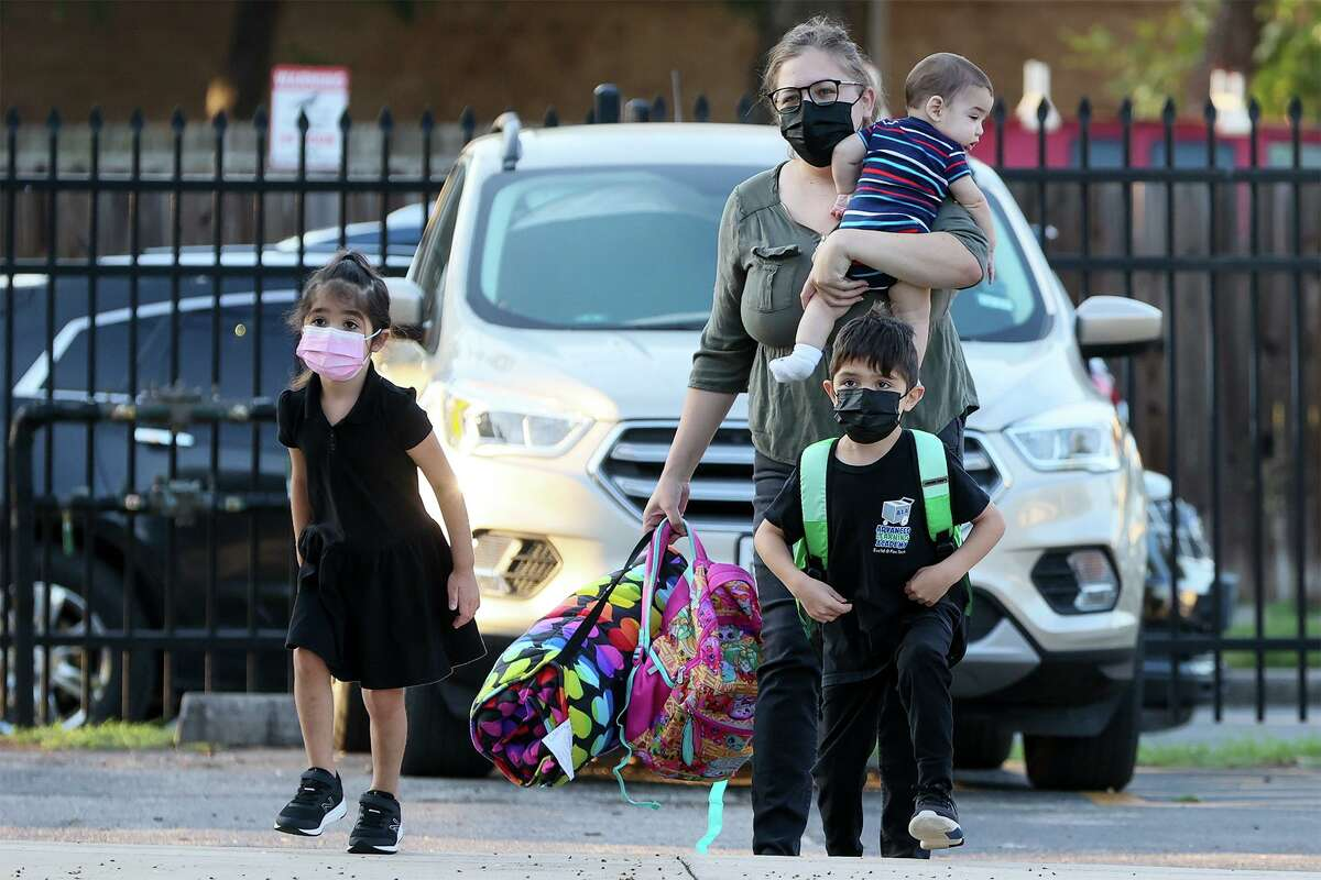 Anita Martinez brings her children Claire, 4, left, and Roman, 6, to SAISD's Advanced Learning Academy at Euclid while carrying their little brother Marco on Monday.