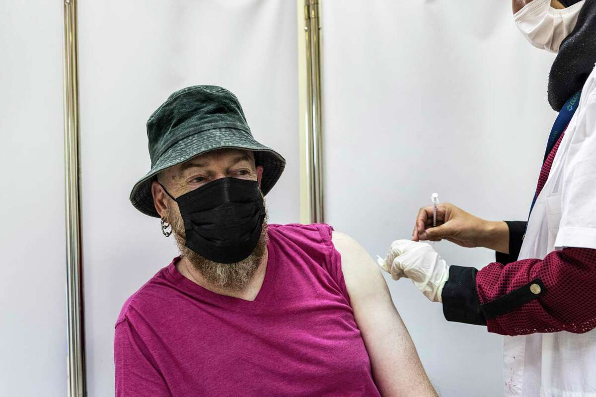 A Bedouin paramedic swabs her patient for a coronavirus vaccine booster shot at a medical center in the Bedouin town of Rahat in the southern Negev, Israel, Monday, Aug. 16, 2021. (AP Photo/Tsafrir Abayov)