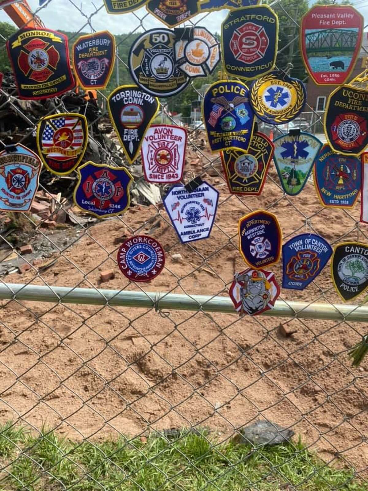 Firefighters put their company or department patches on a fence outside the site of the New Hartford House to show their support for the Burlington Fire Company, whose member Colin McFadden died after fighting the Aug. 10 blaze.